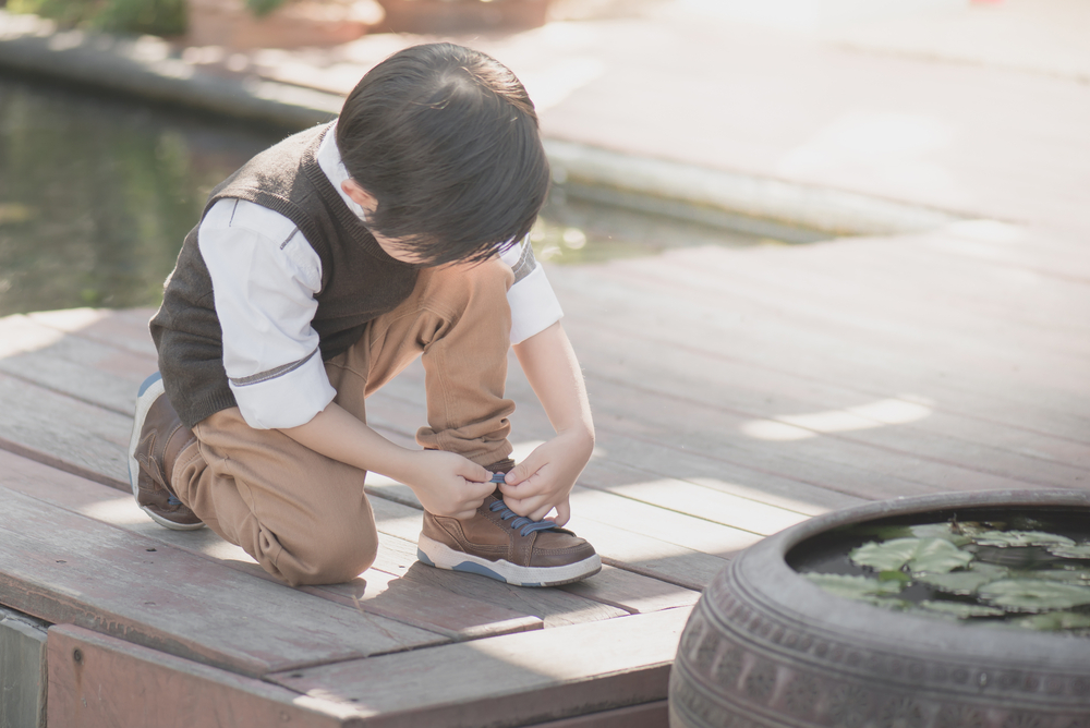 little asian boy tying shoe laces outdoors