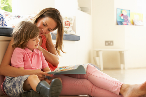 young mum reading book with son